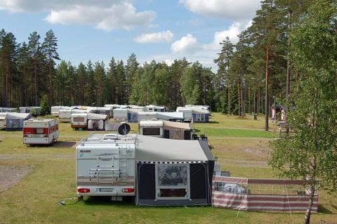 Campa bland lövträd vid Hjälmaren Campingkollen Husvagn